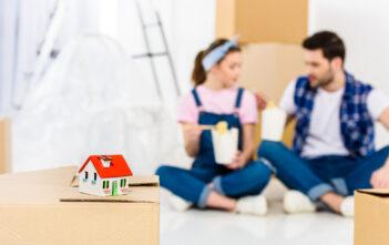 Kærestepar sidder på gulvet i deres nye hus